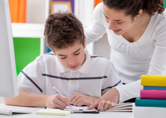 older sister helps brother with a homework
